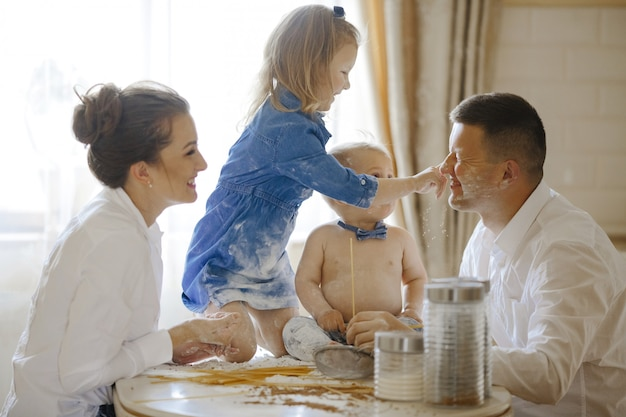 Família feliz junto preparando o pão