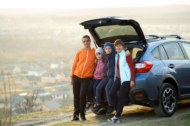 Família feliz juntos de pé perto de um carro com porta-malas aberto, apreciando a vista da natureza da paisagem rural.