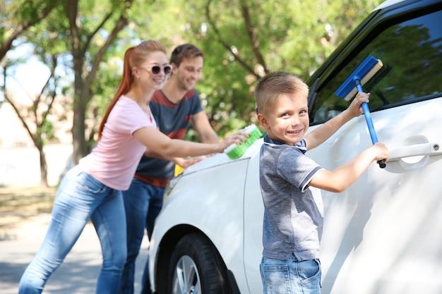 Família feliz lavando carro na rua