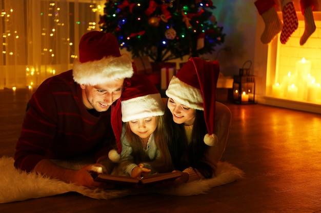 Família feliz lendo livro na sala decorada para o natal