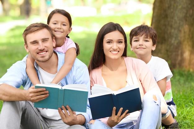 Família feliz lendo livros no parque