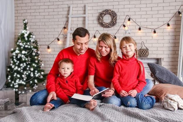 Família feliz lendo um livro em casa no natal
