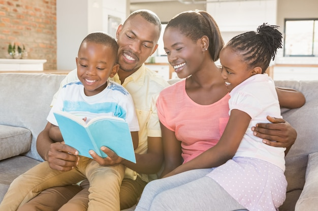 Família feliz lendo um livro juntos na sala de estar