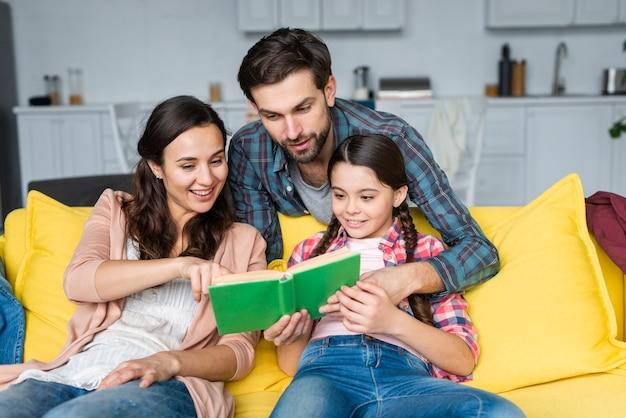 Família feliz, lendo um livro