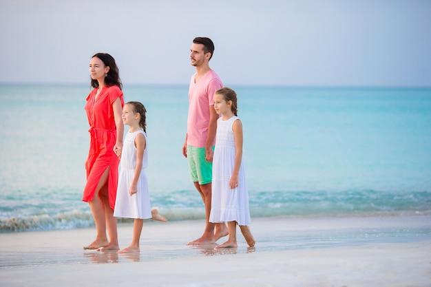 Família feliz linda em uma praia durante as férias de verão