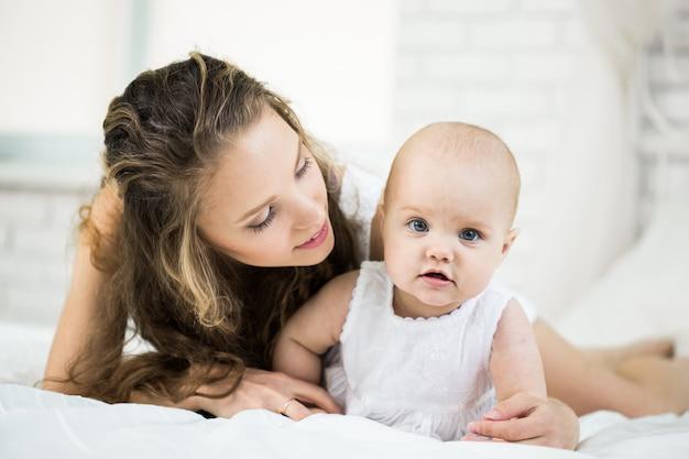Família feliz. mãe brincar com o bebê no quarto.