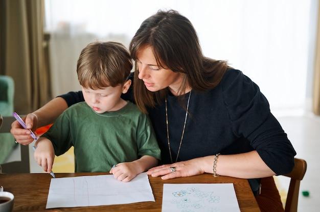Família feliz. mãe com filho pequeno pintando e desenhando juntos. menino branco com a mãe estudando em casa