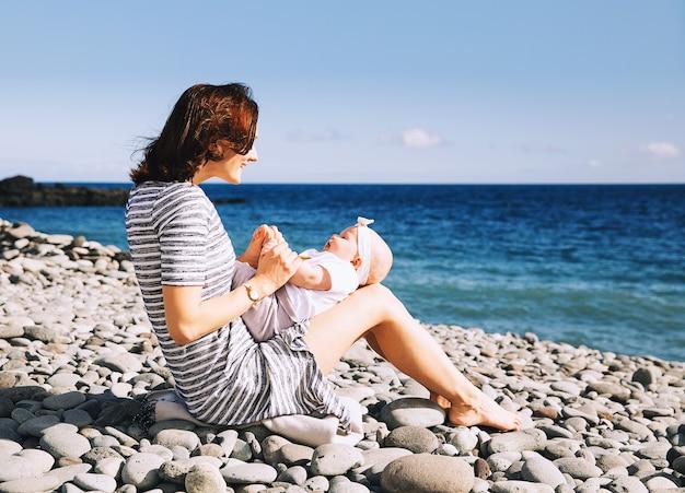 Família feliz mãe e bebê brincando ao ar livre na praia do mar retrato mãe amorosa com filha