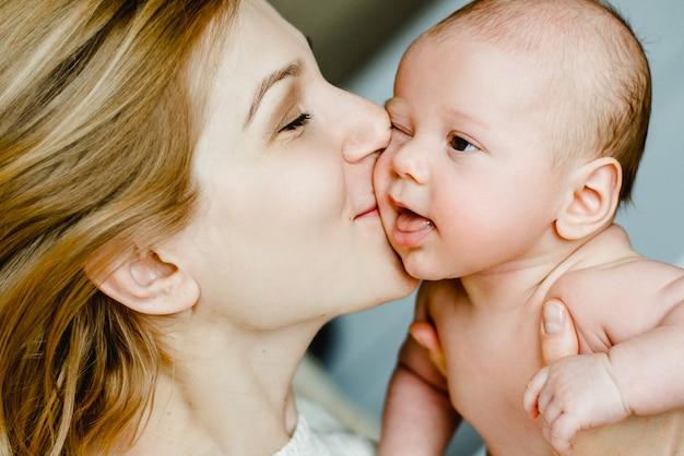 Família feliz mãe e bebê se divertindo brincando, beijando rindo na cama