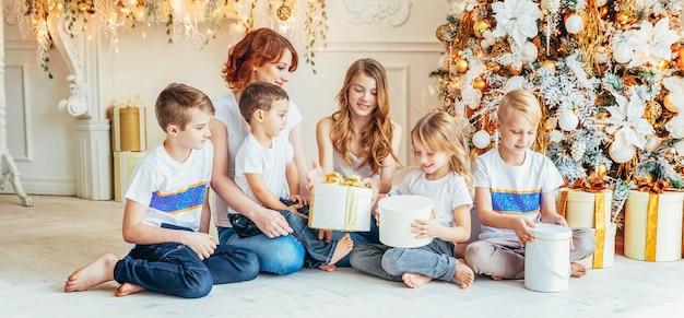 Família feliz, mãe e cinco filhos relaxando brincando perto da árvore de natal em casa