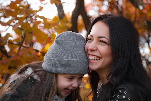 Família feliz, mãe e filha brincando e rindo da caminhada de outono