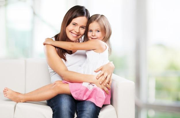 Família feliz. mãe e filha brincando em casa no sofá