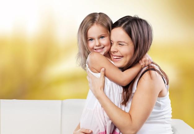 Família feliz. mãe e filha brincando, se abraçando, se beijando em casa no sofá