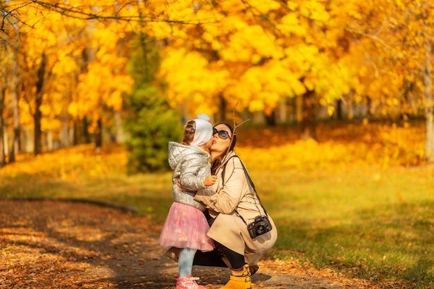 Família feliz, mãe e filha em roupas da moda, caminhando no parque e se beijando em um lindo parque de outono com folhagem amarela de outono em um dia ensolarado