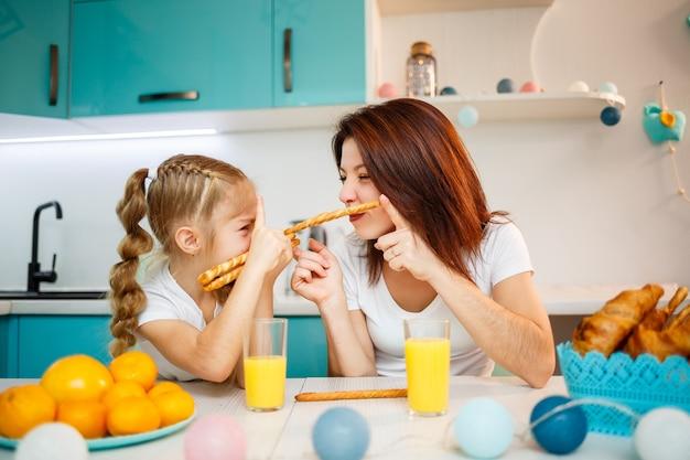 Família feliz, mãe e filha estão sentadas na cozinha e comendo palitos de pão. relações familiares da criança com os pais