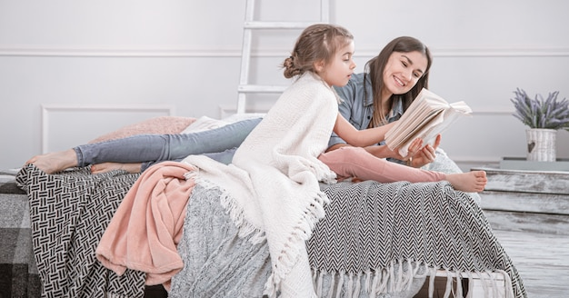 Família feliz. mãe e filha lendo um livro na cama.