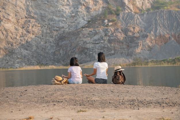 Família feliz, mãe e filha meditando ao ar livre perto do lago