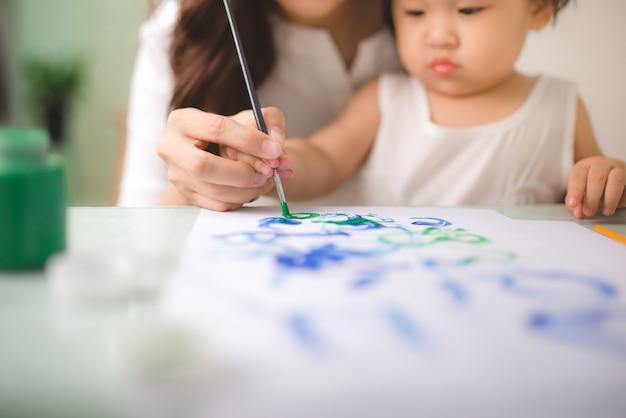 Família feliz mãe e filha pintam juntos. mulher asiática ajuda a filha dela.