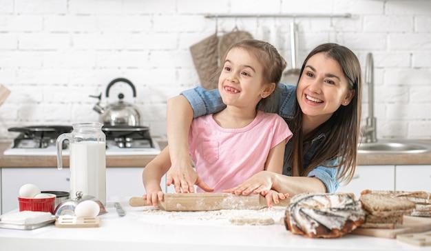 Família feliz. mãe e filha preparam bolos na cozinha.