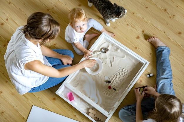 Família feliz, mãe e filhos brincando de brinquedos de materiais ecológicos de desenvolvimento de caixa de areia cinética em casa