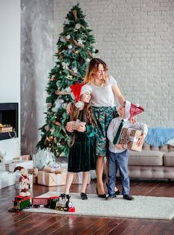 Família feliz, mãe e filhos descompactam presentes debaixo da árvore de natal, sentado junto à lareira, manhã de natal.