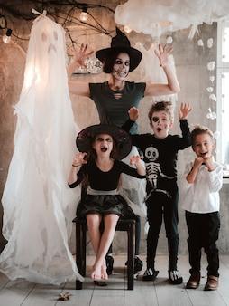 Família feliz, mãe e filhos fantasiados e maquiados na celebração do halloween no cenário ghost, festa de carnaval