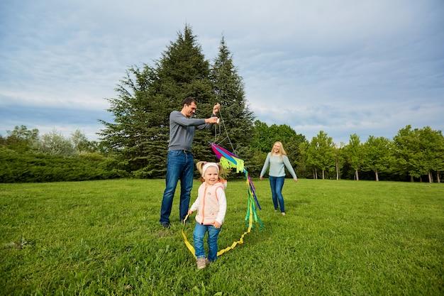 Família feliz, mãe e pai filhos correndo sobre um prado verde empinando uma pipa colorida