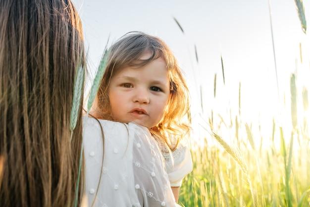 Família feliz, mãe em um vestido com um bebezinho em um campo de trigo dourado ao pôr do sol. dia de verão.