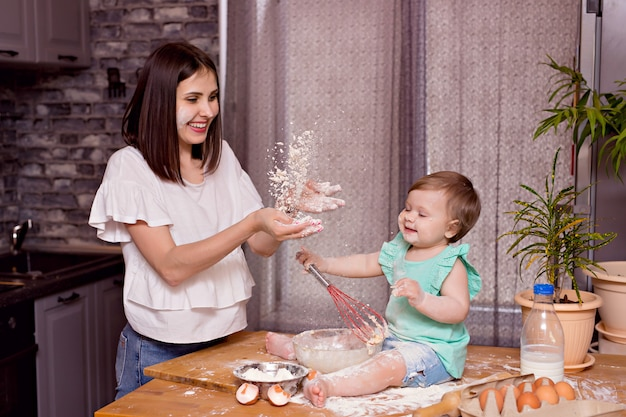Família feliz, mãe, filha brincar e cozinhar na cozinha, sove a massa e assar biscoitos