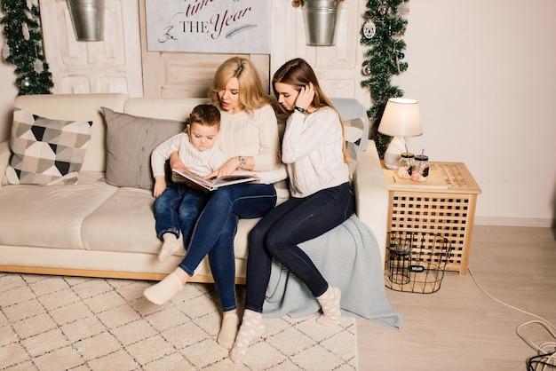 Família feliz mãe, filha e filho em uma árvore de natal em casa