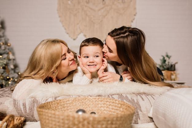 Família feliz mãe, filha e filho na árvore de natal em casa