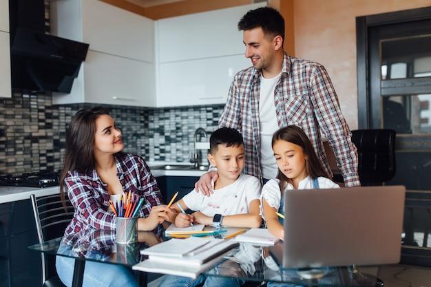Família feliz, mãe morena com pai e filhos adoráveis fazendo lição de casa para a escola