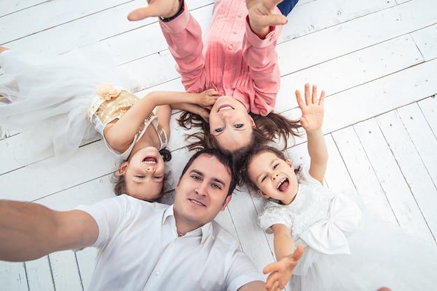 Família feliz mãe, pai e duas irmãs gêmeas em casa em um piso de madeira branco, fazendo um selfie.