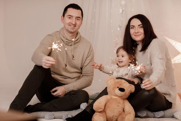 Família feliz, mãe, pai e filha com estrelinhas perto de árvore de natal e lareira em casa.