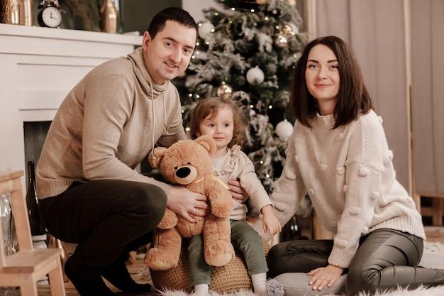 Família feliz, mãe, pai e filha com ursinho de pelúcia perto da árvore de natal e a lareira em casa.