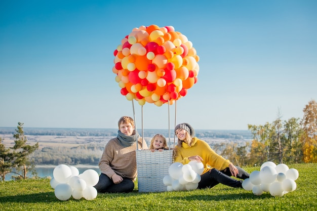 Família feliz, mãe, pai e filha juntos na natureza com balão para viagens aéreas