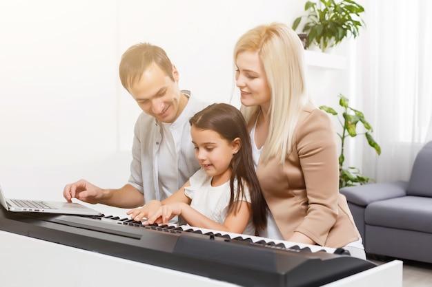 Família feliz, mãe, pai e filha tocando piano em casa, conceito de relacionamento familiar. escola de música e família de música. Foto Premium