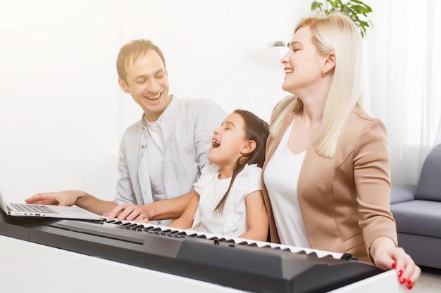 Família feliz, mãe, pai e filha tocando piano em casa, conceito de relacionamento familiar. escola de música e família de música.