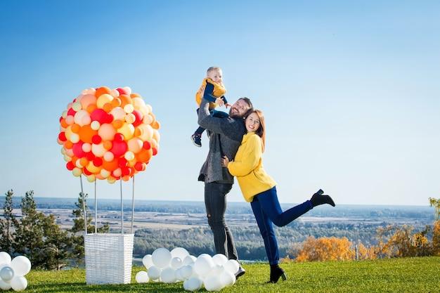 Família feliz, mãe, pai e filho juntos na natureza com balão para viagens aéreas