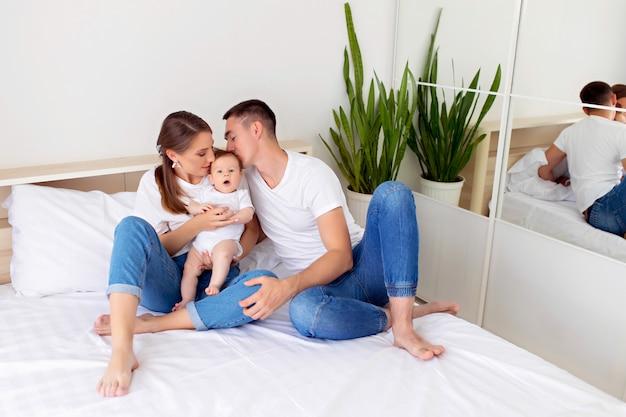 Família feliz: mãe, pai e filho menino deitar em uma cama branca no quarto.