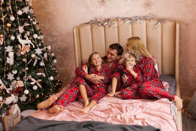 Família feliz mãe pai e filhos na manhã de natal na cama de pijama
