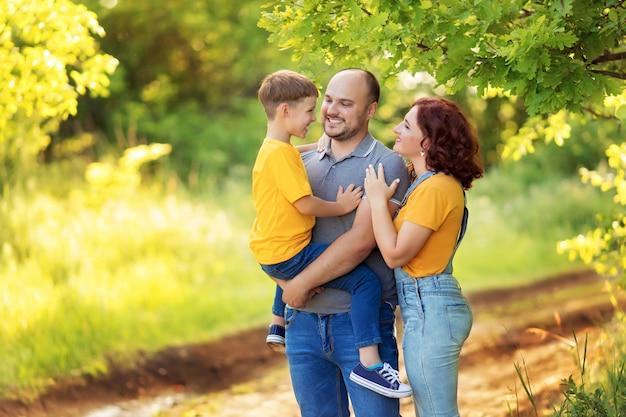 Família feliz, mãe, pai, filho estão andando, abraçando-se ao ar livre no verão.