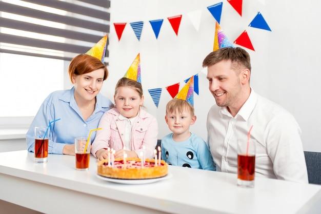 Família feliz, mãe, pai, filho, filha comemorando a festa de aniversário infantil com o bolo.