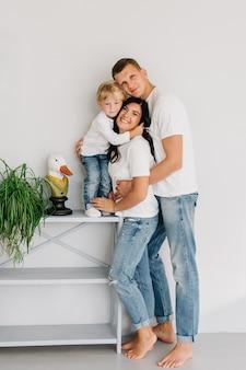 Família feliz, mãe, pai, filho, se abraçam, busto de ganso e flores em casa. o conceito de uma família feliz.