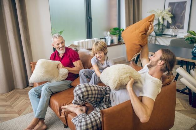 Família feliz. menino loiro fofo e dois homens se divertindo juntos