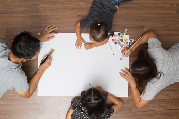 Família feliz, mentindo chão, com, quadro, usando, aquarelas
