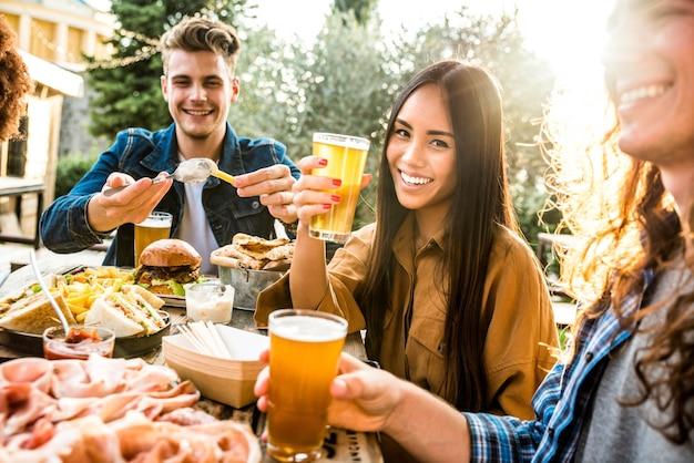 Família feliz mestiça jantando juntos ao ar livre - jovens se divertindo no terraço bebendo cervejas e conversando - amigos multiculturais comemorando festa em casa - conceito de amizade