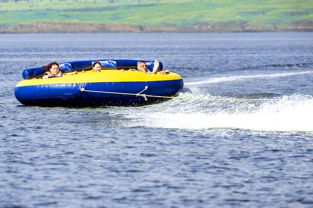 Família feliz monta um pãozinho atrás de um barco, não no lago shira