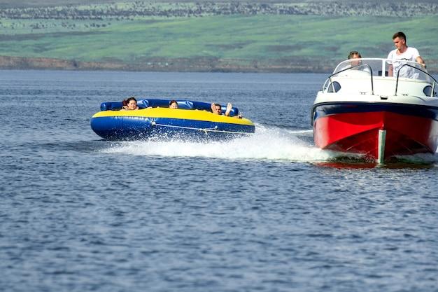 Família feliz montando um coque atrás de um barco