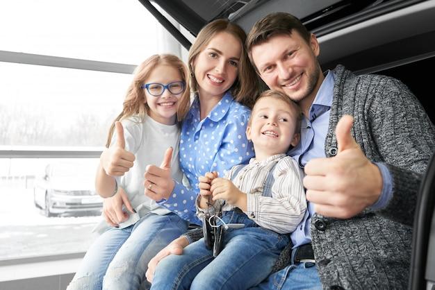 Família feliz mostrando sinal ok no salão do automóvel